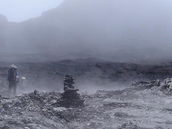 A gray, barren landscape of lava rock and smoke meets the eye.  Two backpackers weave their way towards the base of the volcano.